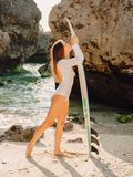 Surfer woman posing with surfboard. Beautiful surfer girl royalty free stock images