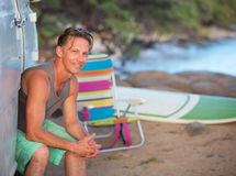 Happy Surfer Sitting at Beach Stock Photos