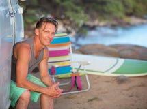 Happy Surfer Sitting at Beach. Male European surfer sitting in van door on beach Stock Photos