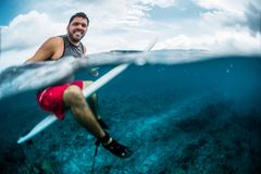 Happy surfer waits the wave on line up. With surf board. Split shot of the surfer with underwater view of the reef Royalty Free Stock Photo