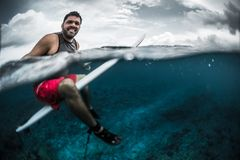 Happy surfer waits the wave on line up. With surf board. Split shot of the surfer with underwater view of the reef Royalty Free Stock Photography