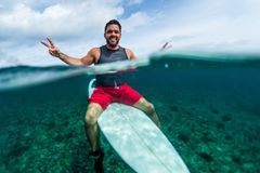 Happy surfer waits the wave on line up. With surf board looks at camera and shows the Peace signs Royalty Free Stock Photography