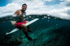 Happy surfer waits the wave on line up. With surf board. Split shot of the surfer with underwater view of the reef Stock Images