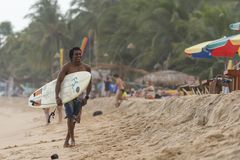 Happy surfer walking on the beach. Local surfer walking on the beach in Arugam Bay, Sri Lanka. Arugam Bay is the hotspot in Sri Lanka and probably one of the Stock Image