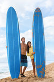 Happy surfers surfing couple posing with surfboard. Happy young couple surfers posing with long surfboard on hawaii beach after surf class. Male surfing stock image