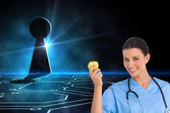 Happy surgeon holding an apple and smiling at camera Stock Photo