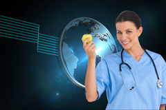Happy surgeon holding an apple and smiling at camera Royalty Free Stock Images