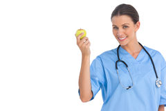 Happy surgeon holding an apple and smiling at camera Stock Images
