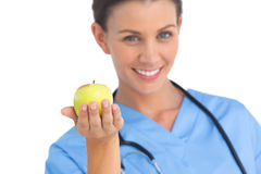 Happy surgeon holding an apple and smiling Royalty Free Stock Photos