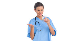 Happy surgeon holding medicine and glass of water Stock Photography