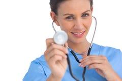 Happy surgeon holding up stethoscope Royalty Free Stock Photography