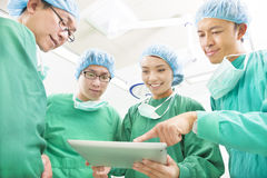 Happy Surgeons discussing success operating procedure. With tablet at hospital Royalty Free Stock Photo
