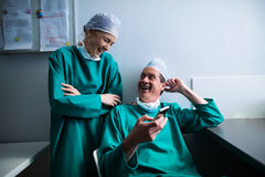 Happy surgeons interacting while using mobile phone. Of hospital Stock Photo