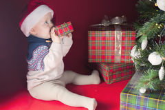 Happy surprised baby holding gift box, present, Christmas, eve Stock Images