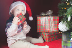 Happy surprised baby holding gift box, present, Christmas, eve Royalty Free Stock Images