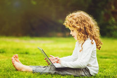 Happy surprised child with laptop sitting on the grass. Stock Photos