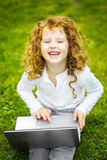 Happy surprised child with laptop sitting on the green grass. Royalty Free Stock Photography