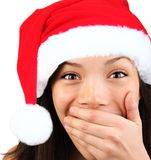 Happy surprised christmas woman. Christmas girl very excited and surprised holding her mouth. Beautiful mixed asian / caucasian model Stock Photo
