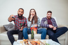 Happy surprised friends watching tv at home together Royalty Free Stock Images