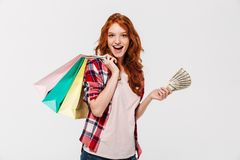 Happy Surprised ginger woman in shirt holding packages. And money while looking at the camera over gray background royalty free stock photos