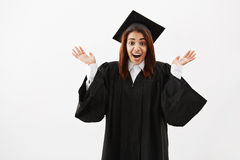 Happy surprised girl graduate gesturing looking at camera over white background. Royalty Free Stock Photography