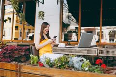 Happy surprised girl in outdoors street coffee shop cafe sitting at table with laptop computer, texting message on. Happy smiling girl in outdoors street coffee royalty free stock photo