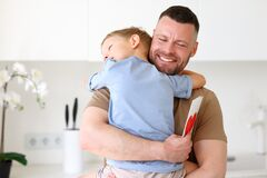 Little boy son giving dad greeting postcard with drawn red heart on Fathers Day