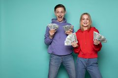 Happy surprised people, handsome man in purple hoodie and beautiful blonde girl in red hoodie standing together with stock photos