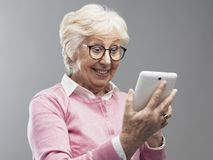 Happy surprised senior lady using a digital tablet stock photos