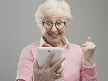 Happy surprised senior lady using a digital tablet. Cheerful senior lady using a digital tablet and receiving an amazing surprise, she is a winner and royalty free stock image