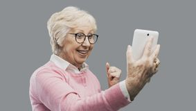 Happy surprised senior lady using a digital tablet. Cheerful senior lady using a digital tablet and receiving an amazing surprise, she is a winner and stock photos