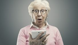 Happy surprised senior lady using a tablet. Happy surprised senior woman using a digital tablet, she has received an amazing surprise online royalty free stock photo