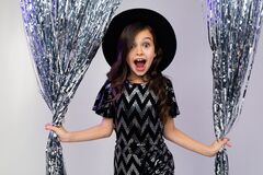 Happy Surprised Teenager Girl In A Black Hat And Elegant Dress On A Background Of Shiny Rain Royalty Free Stock Image