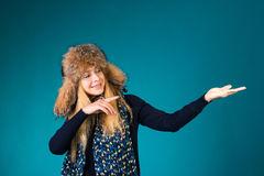 Happy surprised winter woman showing pointing on empty copyspace. Stock Images