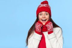Happy surprised woman looking sideways in excitement. Christmas girl wearing knitted warm hat and mittens, isolated on blue stock photos