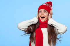 Happy surprised woman looking sideways in excitement. Christmas girl wearing knitted warm hat and mittens, isolated on blue backgr Royalty Free Stock Photography