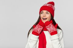 Happy surprised woman looking sideways in excitement. Excited christmas girl wearing knitted warm hat and scarf, isolated on gray. Background royalty free stock image