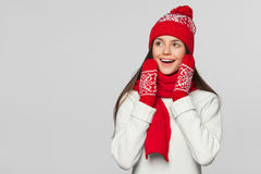 Happy surprised woman looking sideways in excitement. Excited christmas girl wearing knitted warm hat and scarf, isolated on gray Royalty Free Stock Photography