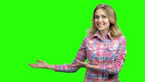 Happy surprised woman showing product on green screen.