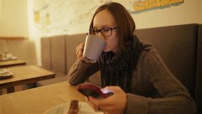 Happy, surprised woman using smartphone sitting in cafe. Young caucasian girl in glasses typing sms and drinking coffee. Happy, surprised woman using smartphone stock video