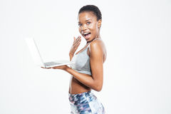 Happy surprised young african american sportswoman holding laptop. Over white background royalty free stock images