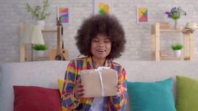 Happy and surprised young African American woman with Afro hairstyle. Sitting on the couch in the living room holding a gift box stock video