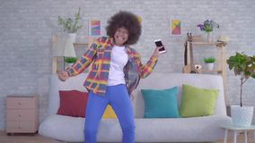 Happy and surprised young African American woman with Afro hairstyle looks at the phone and enjoys winning slow mo. In the living room stock video