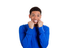 A happy and surprised young man with both fists near his chin Royalty Free Stock Image