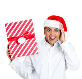 A happy and surprised young man in santa's hat Stock Photo