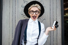 Happy surprised young woman photographer holding photo camera Royalty Free Stock Photos