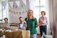 Happy young woman receiving a gift on indoor party. royalty free stock images