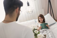 Bringing breakfast on a tray. Happy and surprised young women lying in bed in the morning while her husband is bringing her breakfast and flowers on a tray Stock Photos
