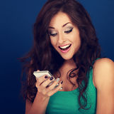 Happy surprising makeup young woman looking on mobile phone with Stock Photography