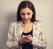 Happy surprising woman looking in mobile phone and reading sms w Stock Photos
